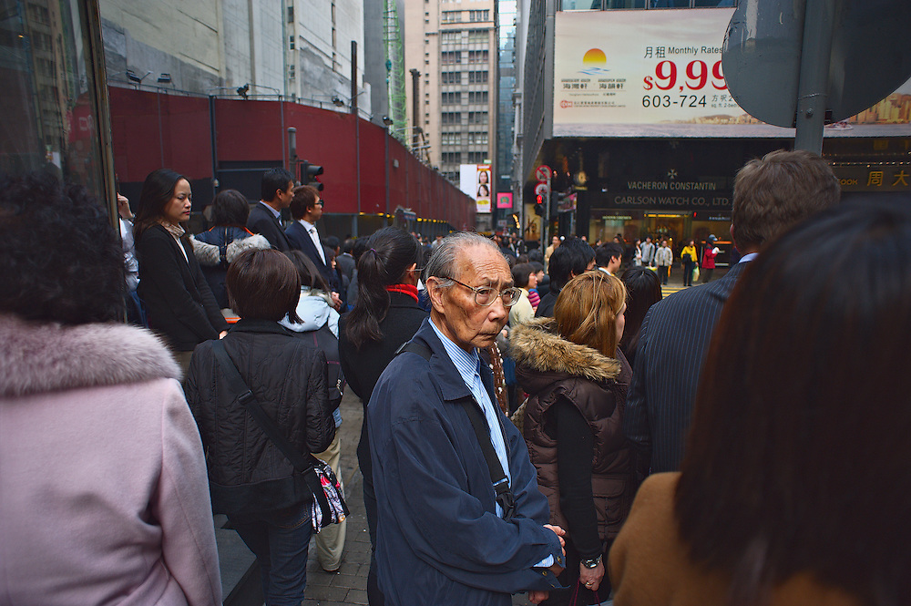 Old man at crowded street corner, Hong Kong's Central district
