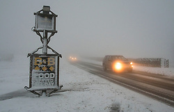 © Licensed to London News Pictures. 27/01/2014 North York Moors, England Motorists drive through early morning snow and fog as they pass the Lion Inn pub high up on Blakey Ridge on the North York Moors after another night of snow. Photo credit : Ian Forsyth/LNP