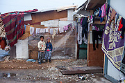 Children in front of their home at the area of Konik Camp located in the suburbs of the city of Podgorica, Montenegro. A huge fire in 2012 detroyed a big part of the refugee camp and many of the inhabitants are living in containers. The housing pictured belongs still to the part with old housing facilities.