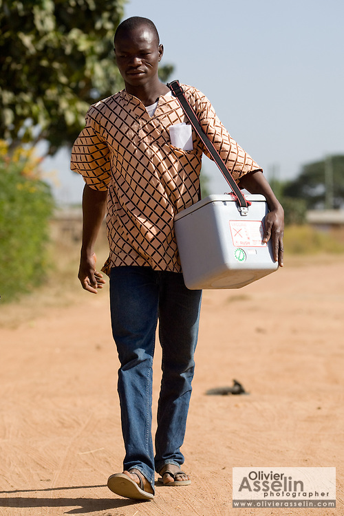 Member of a vaccination team walking through village carrying an ice box with polio vaccines. Northern Ghana, Thursday November 13, 2008.