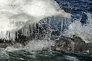 Water splashing on rocks with snow and icicles.