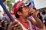 """07 MAY 2010 - BANGKOK, THAILAND: A Thai Red Shirt protester blows his noisemaker in Ratchaprasong intersection, Friday May 7, more than one month after the Reds occupied the intersection. Members of the United Front of Democracy Against Dictatorship (UDD), also known as the """"Red Shirts"""" and their supporters moved their anti government protests into central Bangkok Apr. 4 when they occupied Ratchaprasong intersection, the site of Bangkok's fanciest shopping malls and several 5 star hotels. The Red Shirts are demanding the resignation of current Thai Prime Minister Abhisit Vejjajiva and his government. The protest is a continuation of protests the Red Shirts have been holding across Thailand. They support former Prime Minister Thaksin Shinawatra, who was deposed in a coup in 2006 and went into exile rather than go to prison after being convicted on corruption charges. Thaksin is still enormously popular in rural Thailand. This move, away from their traditional protest site in the old part of Bangkok, has gridlocked the center of the city and closed hundreds of stores and restaurants and several religious shrines.     PHOTO BY JACK KURTZ"""