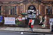 Wendy, a lifelong campaigner and activist stands outside Carnegie Library in Herne Hill, south London asking passing motorists to hoot their support, while occupiers remain inside the premises on day 7 of its occupation, 6th April 2016. The angry local community in the south London borough have occupied their important resource for learning and social hub for the weekend. After a long campaign by locals, Lambeth have gone ahead and closed the library's doors for the last time because they say, cuts to their budget mean millions must be saved.