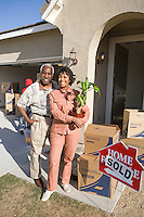Middle-aged couple in front of new house