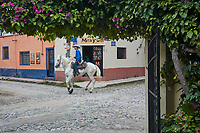 A young Mexican boy rides a grey horse through the streets of Ajijic, Jalisco, Mexico