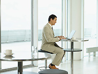 Businessman sitting at table working on laptop side view