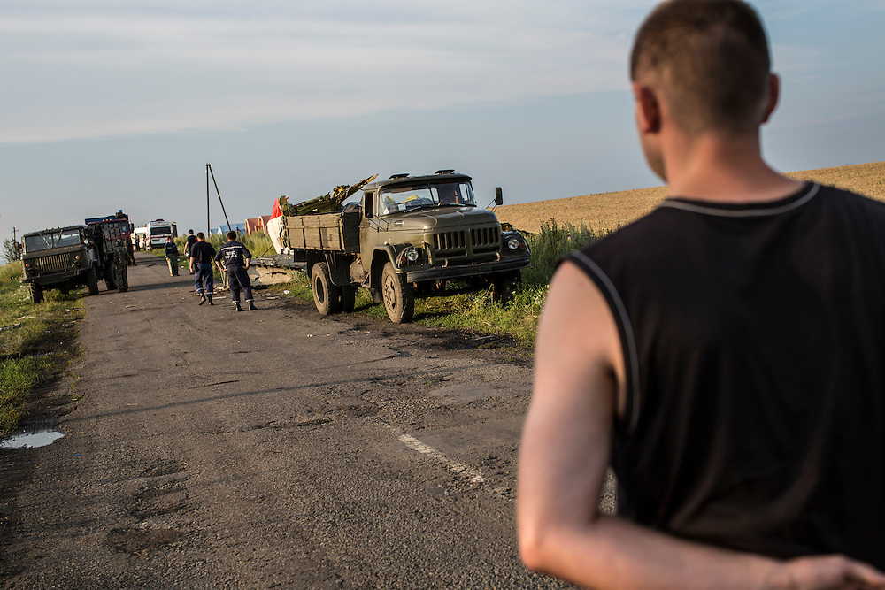GRABOVO, UKRAINE - JULY 19: A man blocks access to the scene of the crash of Malaysia Airlines flight MH 17 as emergency personnel remove the bodies of passengers after pro-Russia separatist fighters established control of the site on July 19, 2014 in Grabovo, Ukraine. Malaysia Airlines flight MH17 was travelling from Amsterdam to Kuala Lumpur when it crashed killing all 298 on board including 80 children. The aircraft was allegedly shot down by a missile and investigations continue over the perpetrators of the attack. (Photo by Brendan Hoffman/Getty Images) *** Local Caption ***