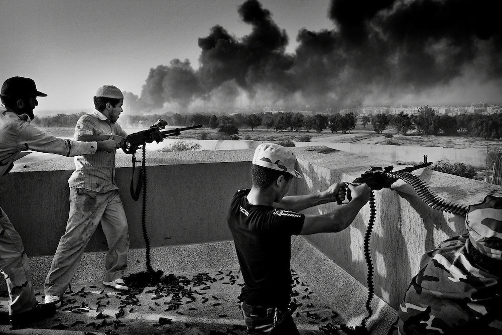 Anti-Qaddafi fighters exchange fire with loyalists to Col. Muammar el-Qaddafi during a heavy gun battle atop of a residential building from the east end, for Qaddafi's hometown city of Sirte, Libya, on October 9, 2011. Photo by Mauricio Lima for The New York Times