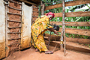 Host home mother Agnes Pascal using her tippy tap outside the toilet in the host home built by the Raleigh ICS volunteers. ICS Raleigh SWASH (school water, sanitation and hygiene plan) project. Mbulu, Manyara district, Tanzania. Working in partnership with the Diocese of Mbulu Development Department (DMDD); part of Caritas Tanzania.