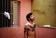 Bare chested man showing off his tattoos, Brazil, 2000's