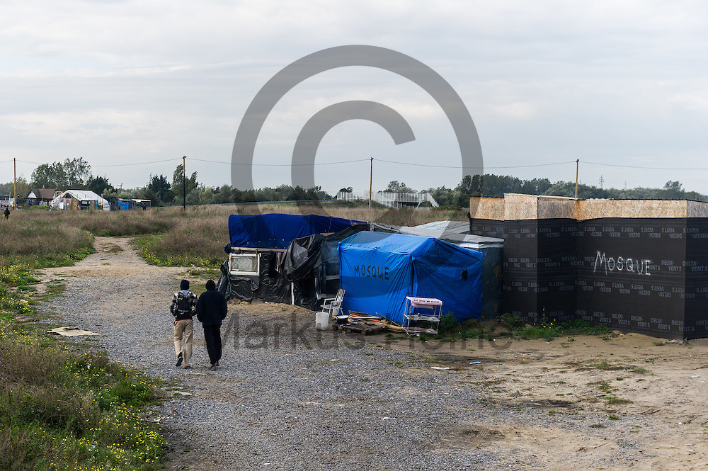 Calais, Frankreich - 16.10.2016<br /> Migranten laufen im Dschungel von Calais an einer Moschee vorbei. Das Fluechtlingscamp an der Kueste zum Aermelkanal soll laut franzoesischer Regierung in den naechsten Tagen geraeumt werden. In dem Camp leben um die 1000 Fluechtlinge und warten auf die Moeglichkeit zur Weiterreise durch den Eurotunnel nach Gro&szlig;britannien. Photo: Foto: Markus Heine / heineimaging<br /> <br /> Calais, France - 2016/10/16<br /> Migrants walk past a Mosque in the Calais Jungle. The refugee camp on the coast to the English Channel is to be cleared in the next few days, according to the French government. In the camp live around the 1000 refugees and wait for the possibility to travel further through the Eurotunnel to the UK. Photo: Foto: Markus Heine / heineimaging<br /> <br /> ------------------------------<br /> <br /> Veroeffentlichung nur mit Fotografennennung, sowie gegen Honorar und Belegexemplar.<br /> <br /> Bankverbindung:<br /> IBAN: DE65660908000004437497<br /> BIC CODE: GENODE61BBB<br /> Badische Beamten Bank Karlsruhe<br /> <br /> USt-IdNr: DE291853306<br /> <br /> Please note:<br /> All rights reserved! Don't publish without copyright!<br /> <br /> Stand: 10.2016<br /> <br /> ------------------------------