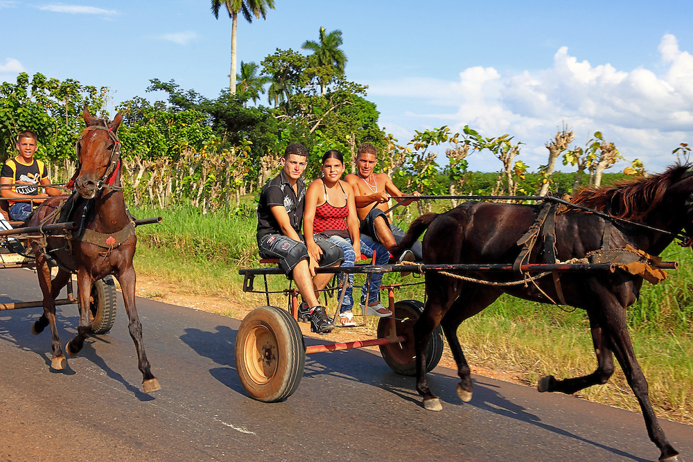 Teenagers racing horses down a country road near Jaruco, Mayabeque Province, Cuba.