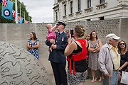 On the 100th anniversary of the Royal Air Force (RAF) and following a flypast of 100 aircraft formations representing Britain's air defence history which flew over central London, a serviceman holds his child next to the memorial to those killed in the 2002 Bali bombing, on 10th July 2018, in London, England.
