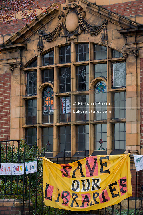 Banners are on the railings and placards are popped up inside the recently-closed Carnegie Library by Lambeth council in Herne Hill, south London as occupiers remain inside the premises on day 3 of its occupation, 3rd April 2016. The angry local community in the south London borough have occupied their important resource for learning and social hub for the weekend. After a long campaign by locals, Lambeth have gone ahead and closed the library's doors for the last time because they say, cuts to their budget mean millions must be saved. A gym will replace the working library and while some of the 20,000 books on shelves will remain, no librarians will be present to administer it.