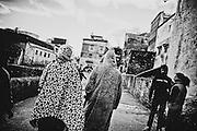 198 / Frau und Mann: AFRIKA, MAR, MAROKKO, CHEFCHAOUEN, Maerz 2010: Frau und Mann spazieren in der Altstadt von Chefchaouen. Chefchaouen, Chaouen oder Xauen ist eine marokkanische Stadt, die Hauptstadt der gleichnamigen Provinz. Sie befindet sich im Nordosten Marokkos, in den Auslaeufern des Rif-Gebirges, in der Naehe von Tetouan. - Marco del Pra / imagetrust - Stichworte: Afrika, Marokko, Maghreb, Maroc, Chefchaouen, Chaouen, Xaouen, Koenigreich, Koenig, Mohammed VI, Medina, Altstadt, Frau, Mann, Turban, Islam, islamisch, Muslim, muslimisch, Arabisch, Berber, Sufi, Sufismus,  Religion, Schwarz, Weiss, Djellaba, Dschellaba, Galabiya, Rif, Gebirge, Tunica, Tradition, Gewand, Leopard, Leopardmuster, Kopftuch, Tuch, Kleid, Frauenkleid, Stoff, Schleier, Orient,