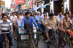 Crowd of cyclists on street in Shanghai during morning rush hour