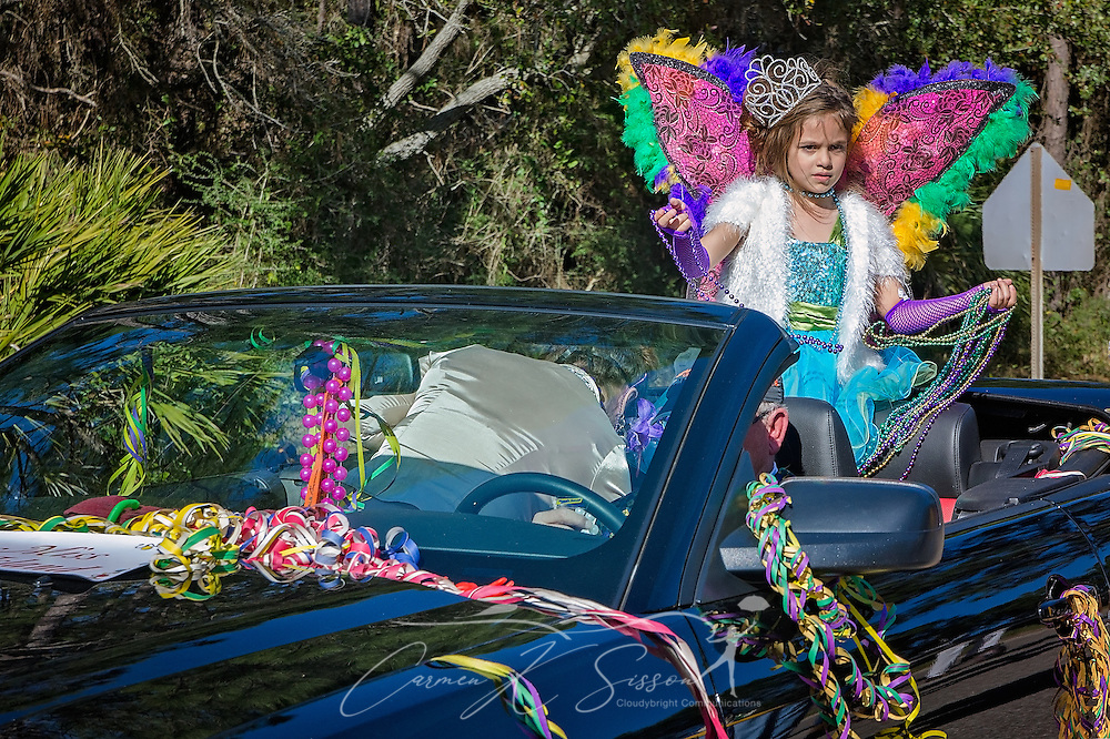 Abigail Robinson, Little Miss Dauphin Island, throws beads as she rides in Dauphin Island's first People's Parade during Mardi Gras, Feb. 4, 2017, in Dauphin Island, Alabama. French settlers held the first Mardi Gras in 1703, making Mobile's celebration the oldest Mardi Gras in the United States. The first parade of the season is traditionally held on Dauphin Island and draws thousands. (Photo by Carmen K. Sisson/Cloudybright)