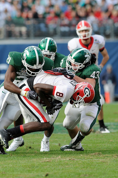 January 1, 2009: A.J. Green of the Georgia Bulldogs is tackled by Otis Wiley, Chris L. Rucker and Eric Gordon of the Michigan State Spartans during the NCAA football game between the Michigan State Spartans and the Georgia Bulldogs in the Capital One Bowl. The Bulldogs defeated the Spartans 24-12.