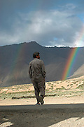 India, Serchu night camp, between Manali and Leh, Kullu District, Himachal Pradesh, Northern India, A trucker and a rainbow in the background
