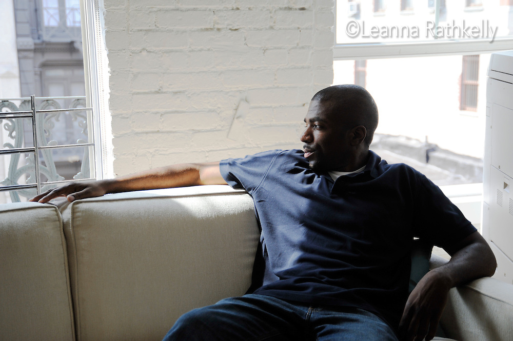 Adult male of african-american race sits on the living room sofa, relaxed and happy.