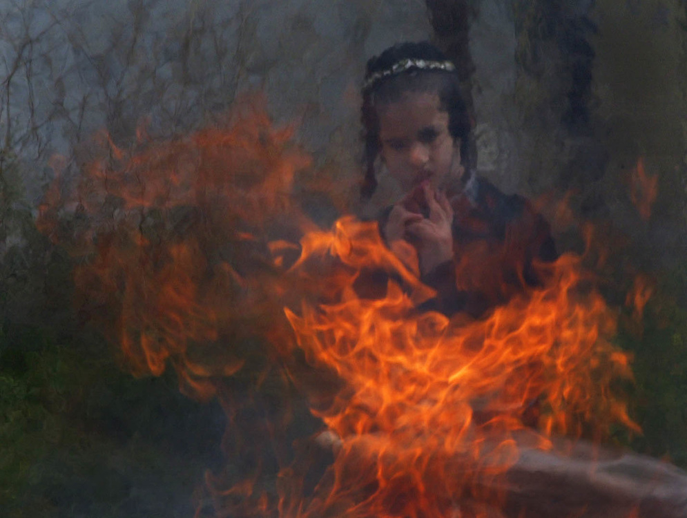 A Jewish boy looks at a bonfire as Ultra-Orthodox Jews burn leavened products before the start at sundown of the Passover festival in Mea Shearim's neighborhood in Jerusalem, Israel April 6, 2001.