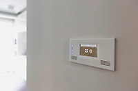 Close up photo of modern temperature touch switch board on wall