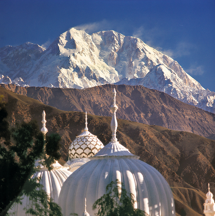 The snow-capped view of Trich Mir Peak, in Chitral, Pakistan, echoes the white dome of this mosque.