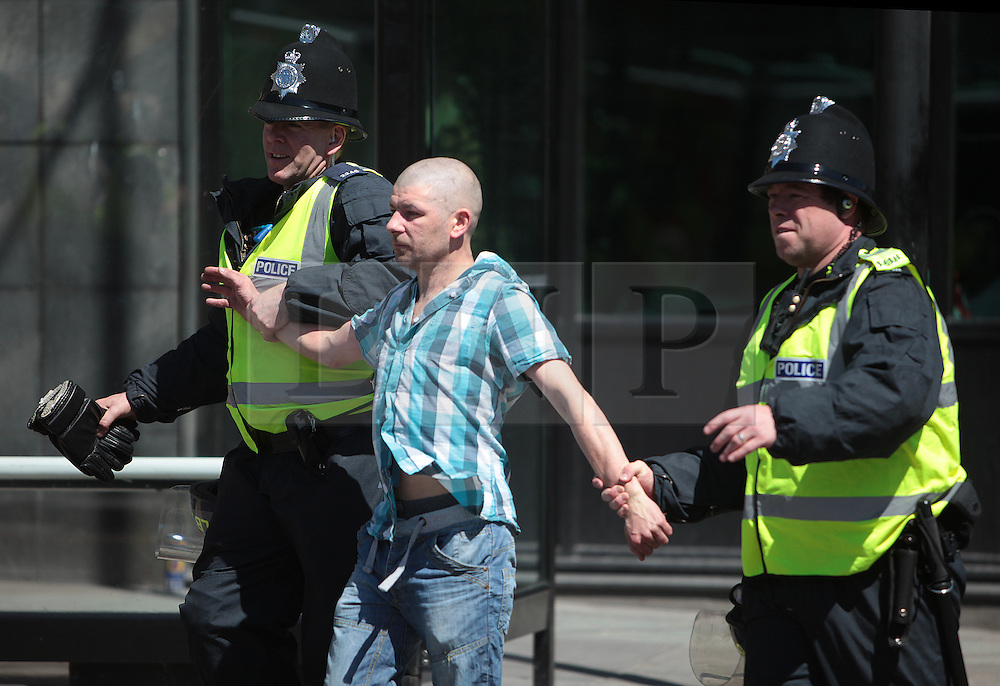 Licensed to London News Pictures. 25/05/2013. Newcastle upon Tyne, UK. An EDL supporter is arrested for disorder as over a thousand supporters of the EDL congregate and hold a protest march in Newcastle upon Tyne, countered by a march held by Newcastle Unites, a collection of groups opposed to the EDL. A heavy police presence kept the groups separated. Photo credit: Adrian Don/LNP