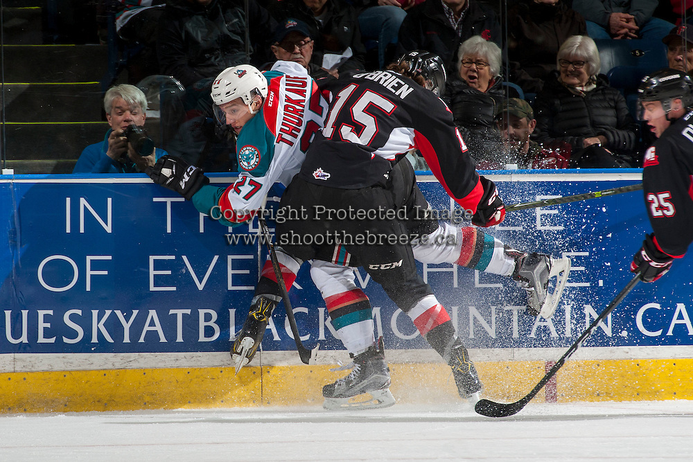 KELOWNA, CANADA - MARCH 1: Brogan O'Brien #15 of the Prince George Cougars checks Calvin Thurkauf #27 of the Kelowna Rockets against the boards during first period on MARCH 1, 2017 at Prospera Place in Kelowna, British Columbia, Canada.  (Photo by Marissa Baecker/Shoot the Breeze)  *** Local Caption ***