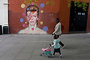 A mother and child walk past the new mural of iconic musician and singer David Bowie has appeared on the wall of Morleys department store in Brixton, Lambeth, south London. The Bowie face is sourced (by artist James Cochran, aka Jimmy C) from the cover of his 1973 album Aladdin Sane at the height of his 1970s fame. The pop icon lived at 40 Stansfield Road, Brixton, from his birth in 1947 until 1953. This cover appeared in Rolling Stone's list of the 500 greatest albums of all time, making #277.