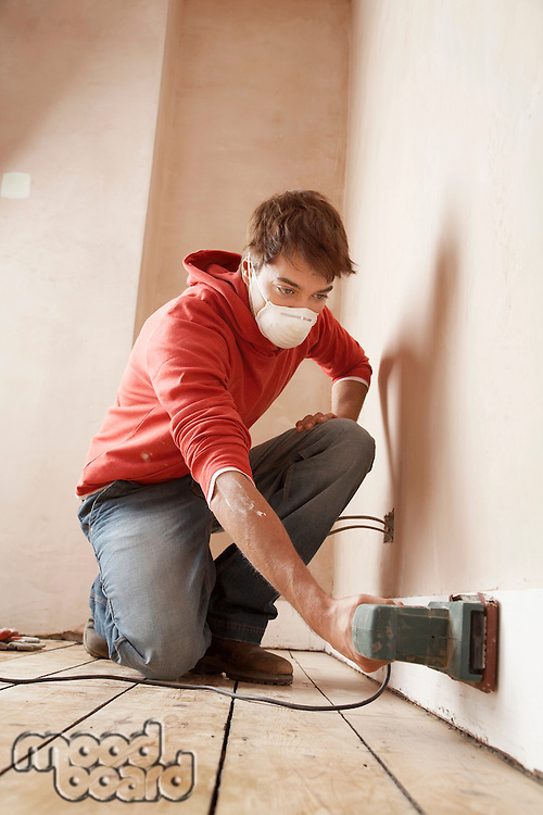 Man wearing face mask sanding wall in unrenovated room low angle view