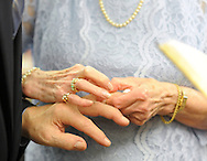 Wesley Enhanced Living Upper Moreland residents, from left, Bud Galow, 90, and Dorothy Dickel, 83, exchange wedding bands during their wedding ceremony Saturday May 28, 2016 in Upper Moreland, Pennsylvania. It is the first wedding ever held at Wesley Enhanced Living. (Photo by William Thomas Cain)