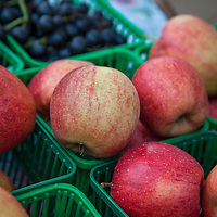 Baskets of tawny,  red apples at a farmers market.