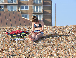 © Licensed to London News Pictures. 12/04/2020. Brighton, UK. A woman sunbathing on Brighton seafront at Brighton and Hove, during a pandemic outbreak of the Coronavirus COVID-19 disease.  Photo credit: Liz Pearce/LNP