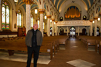 Father Marc Drouin points out the renovations made within Sacred Heart Church in Laconia.  (Karen Bobotas/for the Laconia Daily Sun)