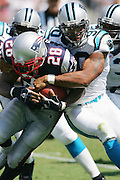 CHARLOTTE, NC - SEPTEMBER 18:  Running back Corey Dillon #28 of the New England Patriots gets tackled by defensive end Julius Peppers #90 of the Carolina Panthers at Bank of America Stadium on September 18, 2005 in Charlotte, North Carolina. The Panthers defeated the Patriots 27-17. ©Paul Anthony Spinelli *** Local Caption *** Corey Dillon;Julius Peppers