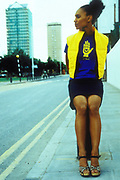 A woman in bright clothing posing on an East London roadside, UK 1990's