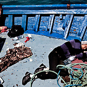 A Northern African refugee lays  stranded in a vessel in the portual area of the Lampedusa Island. Despite the efforts of italian government who evacuated more 600 northen african refugees yesterday by the S. Marco ship, boats continues to attrack in the Island the situation is worsening The portual area of Lampedusa has become a second open air immigration centre where immigrants live in critical igenic and sanitary conditions.