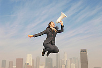 Business woman shouting in bullhorn mid-air above city
