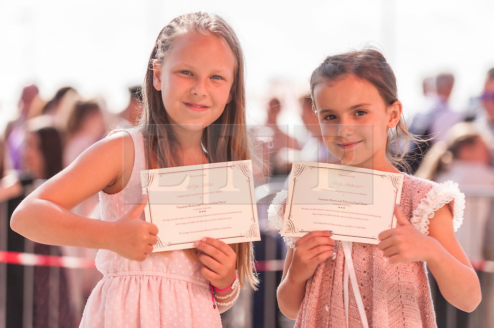 """© Licensed to London News Pictures. 18/07/2015. London, UK. (L to R) Kaitlyn Totten and Emily McClarence, both from Manchester, were the first to arrive in the queue at 4am.  They hold certificates confirming that they took part in the open casting.  Thousands of girls, aged between eight and 12, converge on ExCel London to attend Warner Brothers' open casting for the role of """"Modesty"""" in the forthcoming Harry Potter spin-off, Fantastic Beasts and Where to Find Them.  The studio is searching for a """"haunted young girl with an inner strength and stillness"""".  Whoever is selected will play alongside a star studded cast, including Eddie Redmayne, and with a screenplay written by Harry Potter author, JK Rowling. Photo credit : Stephen Chung/LNP"""