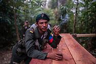 Un guerrillero de las FARC una un cigarrillo en la mitad de la selva mientras bebe café en un recipiente improvisado con una botella de gaseosa. <br /> Photo Federico Rios / Native