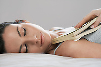 Young woman holding book asleep on bed close-up