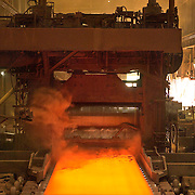 Steel mill press in ambient low light with molten steel