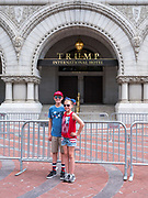 "Two children stand in front of the Trump International Hotel in Washington, D.C. while an adult snaps a picture.  The boy is wearing a ""Make America Great Again"" Hat"