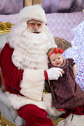 Gemma Marie and Winston Brave see Santa Claus for the first time during the annual breakfast with Santa event, Wednesday, Dec. 20, 2017 at Recreonics Pools of Louisville in Louisville.