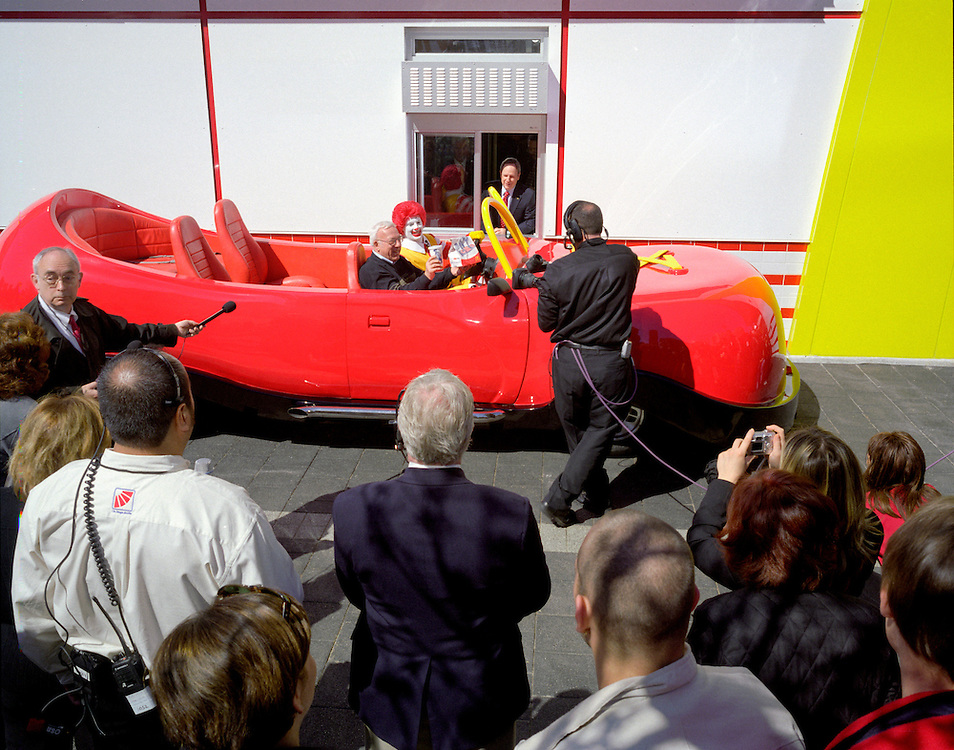 Chicago, Illinois, 2005<br /> <br /> Ronald McDonald picks up carryout at the drive through window of the newly reopened Rock n' Roll McDonald's while driving his famous red shoe car as a gaggle of press record the history making moment.