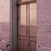 Photograph of an old doorway in an alley.