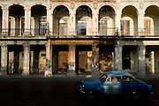A vintage American can drives by run-down colonial buildings in Old Havana, Cuba on Sunday June 29, 2008.