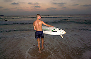 A Palestinian youth holds his surfboard as he gets ready to go in to sea at the Gaza City beach on the Mediterranean coast as the sun goes down Saturday July 28, 2001. Despite the 11 months of violence Israelis and Palestinians take a break to enjoy the Mediterranean beaches and the Dead Sea, where under growing tensions and in the case of Gaza under closure, people try to make the best of their summer and carry on a normal life.