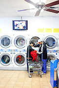 Eduardo Barajas helps his father Roberto take clothes out of the dryer at Coin Laundry in East Point, Georgia December 30, 2009. Monica, Eduardo's mother, has been separated from her husband and son so she could continue dialysis in Mexico.